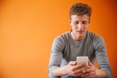 Hombre joven que usa un smartphone Imágenes de archivo libres de regalías