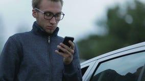 Hombre joven que usa un smartphone almacen de metraje de vídeo