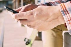 Hombre joven que usa un smartphone al aire libre Foto de archivo libre de regalías