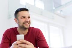 Hombre joven que usa un teléfono móvil en casa Imagen de archivo libre de regalías