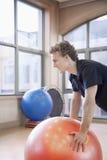 Hombre joven que usa una bola de la aptitud para ejercitar Foto de archivo