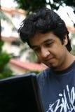 Hombre joven que usa una computadora portátil Imágenes de archivo libres de regalías