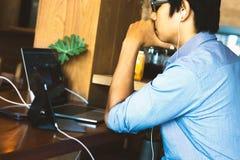 Hombre joven que usa una computadora portátil Fotografía de archivo