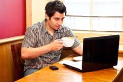 Hombre joven que usa una computadora portátil y bebiendo cappuccino Imágenes de archivo libres de regalías