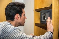 Hombre joven que usa una pequeña cámara acorazada en su hogar fotografía de archivo libre de regalías