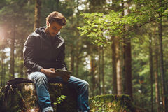 Hombre joven que usa una tableta digital en el bosque Imagen de archivo
