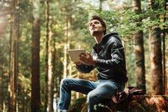 Hombre joven que usa una tableta digital en el bosque Imagenes de archivo