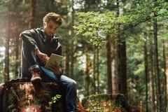Hombre joven que usa una tableta digital en el bosque Foto de archivo