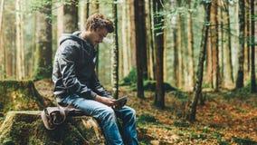 Hombre joven que usa una tableta digital en el bosque Fotografía de archivo