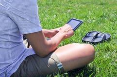 Hombre joven que usa una tableta en un parque fotografía de archivo libre de regalías
