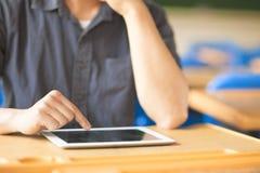 Hombre joven que usa una tableta o un ipad Fotografía de archivo libre de regalías