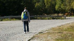 Hombre joven que va abajo del camino vacío en las montañas que miran alrededor, turismo activo almacen de metraje de vídeo