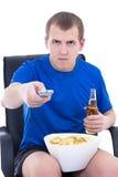 Hombre joven que ve la TV con los microprocesadores y la botella de cerveza aislados encendido Imagen de archivo