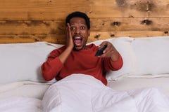 Hombre joven que ve la TV en cama en casa fotografía de archivo