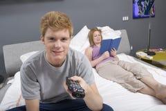 Hombre joven que ve la TV en dormitorio Imagen de archivo