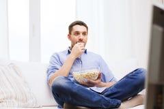 Hombre joven que ve la TV y que come las palomitas en casa Foto de archivo libre de regalías