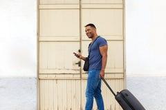 Hombre joven que viaja con la maleta usando el teléfono elegante Fotos de archivo libres de regalías