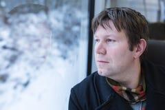 Hombre joven que viaja en tren y que mira hacia fuera la ventana Foto de archivo libre de regalías