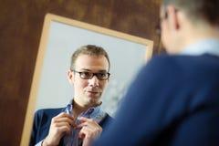 Hombre joven que viste para arriba y que mira el espejo imágenes de archivo libres de regalías