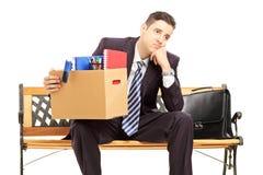Hombre joven redundante decepcionado en un traje que se sienta en un banco foto de archivo libre de regalías