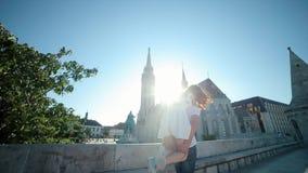 Hombre joven referido los hombros de una sonrisa de giro Matthias Church Background de la mujer