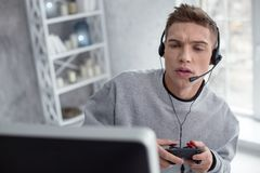 Hombre joven regocijado que juega a los juegos de ordenador Fotografía de archivo