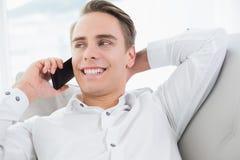 Hombre joven relajado que usa el teléfono móvil en el sofá fotografía de archivo