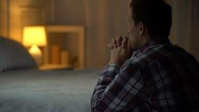 Hombre joven religioso que ruega por la tarde cerca de cama, creencia en dios, cristianismo metrajes
