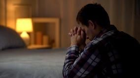 Hombre joven religioso que ruega por la tarde cerca de cama, creencia en dios, cristianismo fotos de archivo