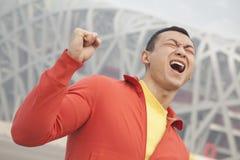 Hombre joven resuelto en ropa atlética con el puño en el aire, con el edificio moderno en el fondo en Pekín, China Imagen de archivo libre de regalías