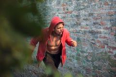 Hombre joven resuelto en una camisa encapuchada roja que se prepara para el entrenamiento fotos de archivo