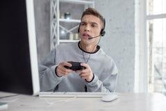 Hombre joven resuelto que juega a los juegos de ordenador Fotos de archivo
