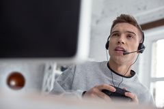 Hombre joven resuelto que juega a los juegos de ordenador Imagenes de archivo