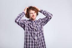 Hombre joven rizado que lleva a cabo su cabeza con emociones negativas en su f fotografía de archivo