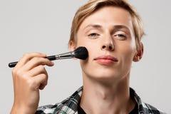 Hombre joven rubio hermoso divertido que lleva la camisa de tela escocesa casual con el cepillo del maquillaje que mira in camera Foto de archivo libre de regalías