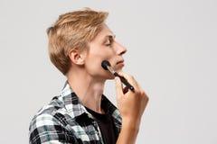 Hombre joven rubio hermoso divertido que lleva la camisa de tela escocesa casual con el cepillo del maquillaje sobre el fondo gri Imagen de archivo