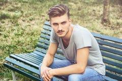 Hombre joven rubio hermoso que se sienta en banco de parque Foto de archivo libre de regalías