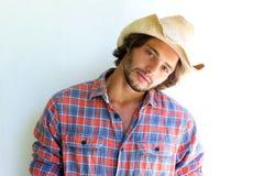 Hombre joven rugoso con la camisa de tela escocesa y el sombrero de vaquero Foto de archivo