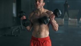 Hombre joven sano que hace el ejercicio para el bíceps Culturista joven que hace el ejercicio pesado para el bíceps cámara lenta  metrajes