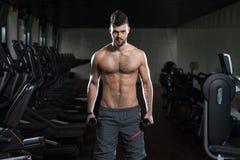 Hombre joven sano que hace el ejercicio para el bíceps Fotografía de archivo