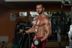 Hombre joven sano que hace el ejercicio para el bíceps Fotos de archivo