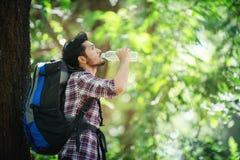 Hombre joven sediento y agua de la bebida durante el viaje detrás de un grande Imagen de archivo