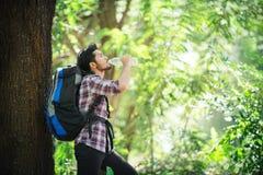 Hombre joven sediento y agua de la bebida durante el viaje detrás de un grande Imagen de archivo libre de regalías