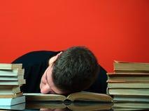 Hombre joven sentido dormido durante estudiar Imágenes de archivo libres de regalías