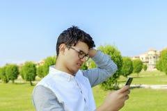 Hombre joven serio al aire libre con el teléfono móvil Imagen de archivo