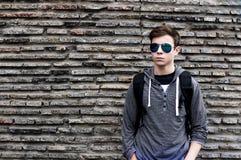 Hombre joven serio cerca de la pared de piedras Fotos de archivo libres de regalías
