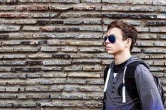 Hombre joven serio cerca de la pared de piedras Foto de archivo libre de regalías