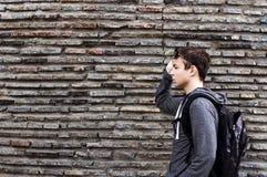 Hombre joven serio cerca de la pared de piedras Imagen de archivo