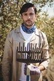Hombre joven serio con el rastrillo que se coloca en la granja verde oliva Imagen de archivo libre de regalías