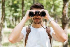 Hombre joven serio con la mochila usando los prismáticos en bosque Fotografía de archivo